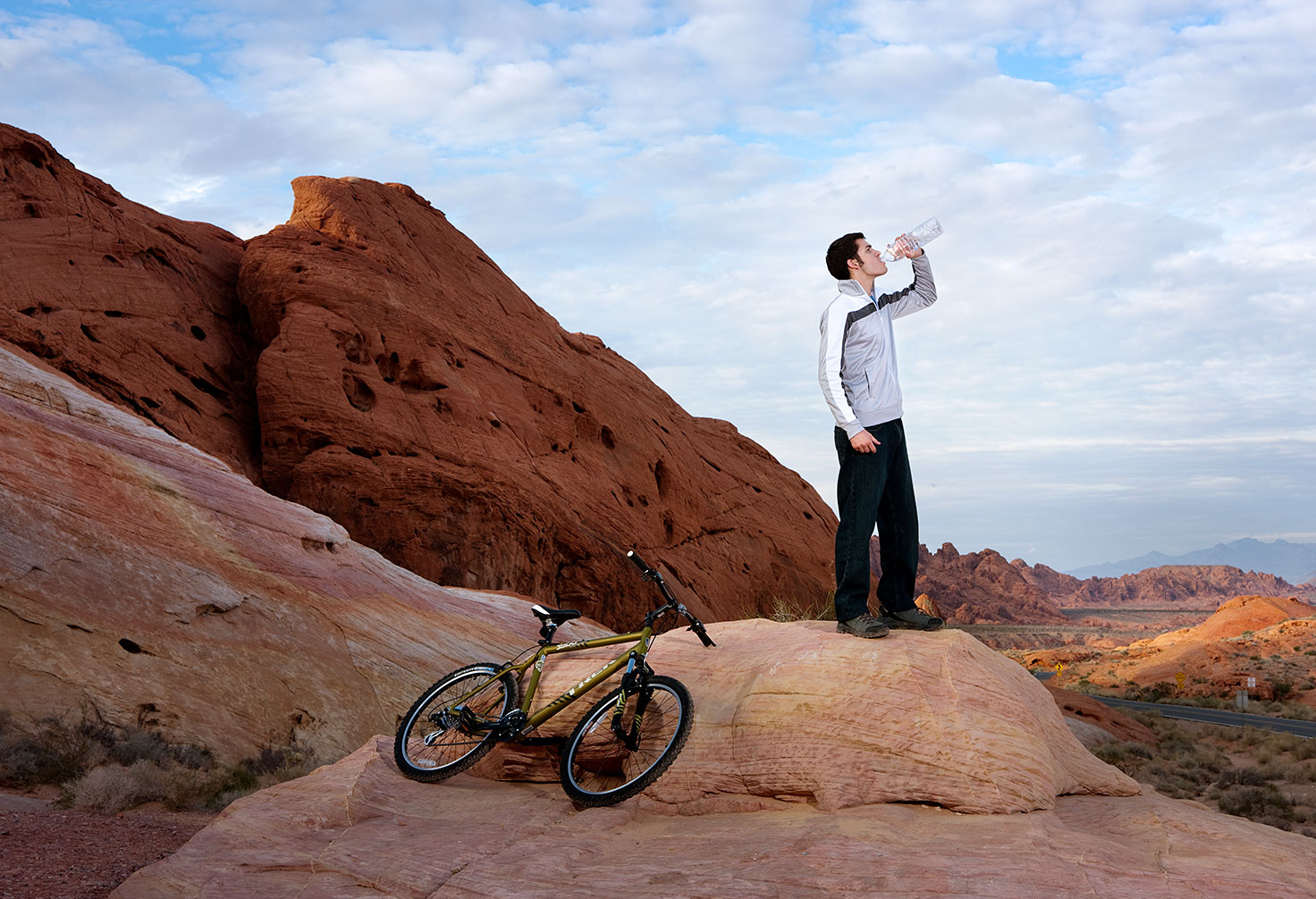 man drinking water after a long bike drive, valley of fire state park, nevada